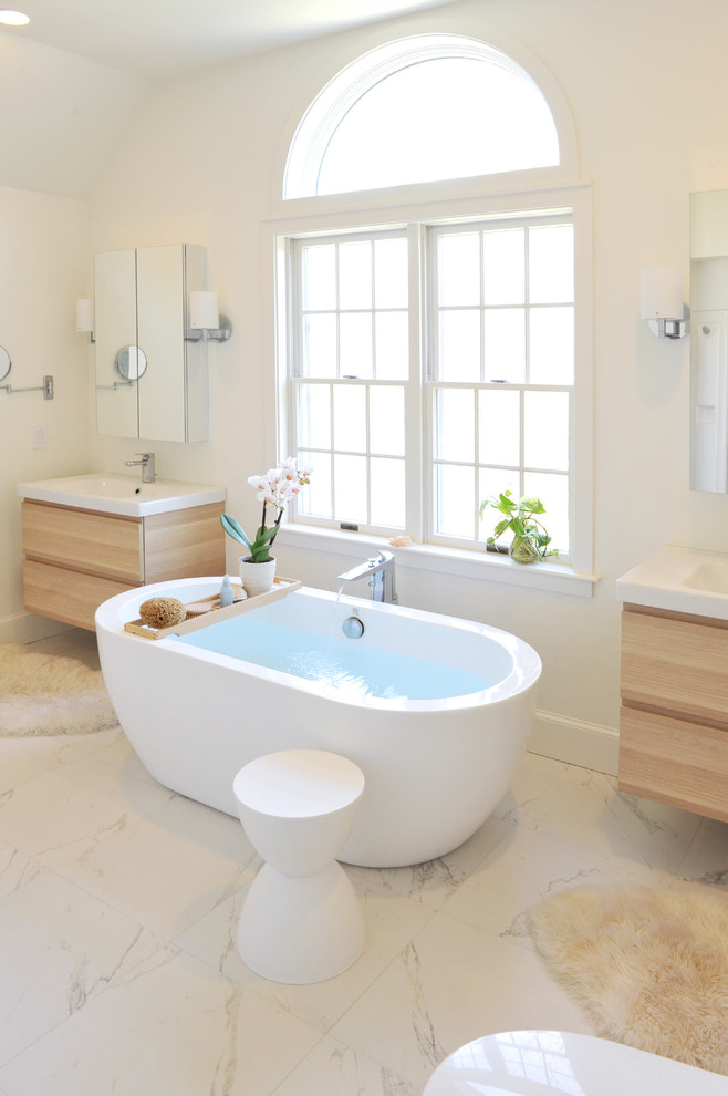 Mid-sized trendy master white tile and ceramic tile marble floor freestanding bathtub photo in Providence with light wood cabinets, white walls, an integrated sink, flat-panel cabinets and a one-piece toilet
