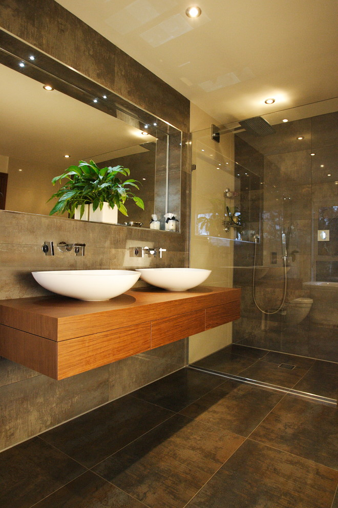 Walk-in shower - contemporary brown tile walk-in shower idea in Dorset with a vessel sink, wood countertops, beige walls and brown countertops