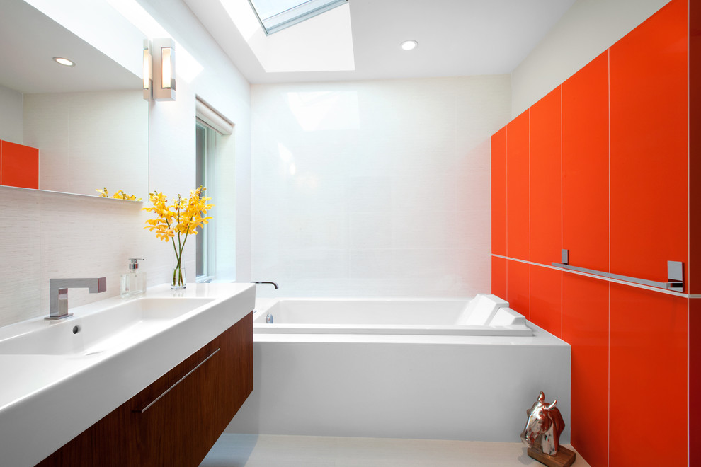 Mid-sized mid-century modern master white tile porcelain tile and gray floor drop-in bathtub photo in Vancouver with an integrated sink, flat-panel cabinets, medium tone wood cabinets, red walls and quartz countertops