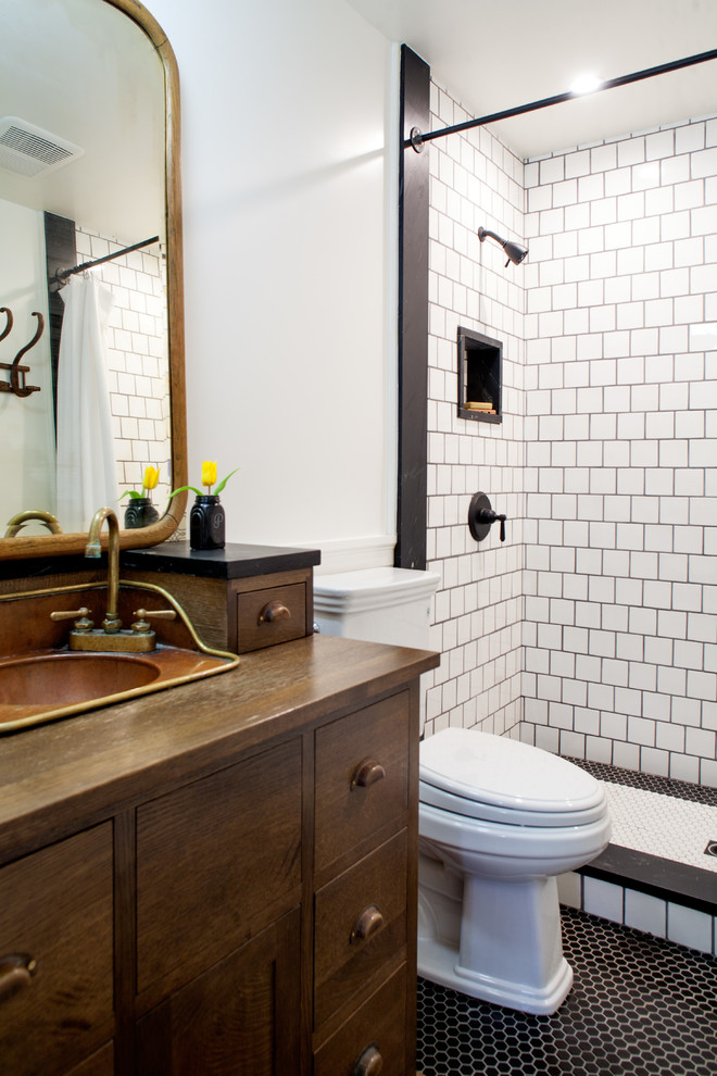 Example of a mid-sized cottage 3/4 ceramic tile and black and white tile mosaic tile floor bathroom design in Los Angeles with a drop-in sink, furniture-like cabinets, dark wood cabinets, wood countertops, a two-piece toilet, white walls and brown countertops