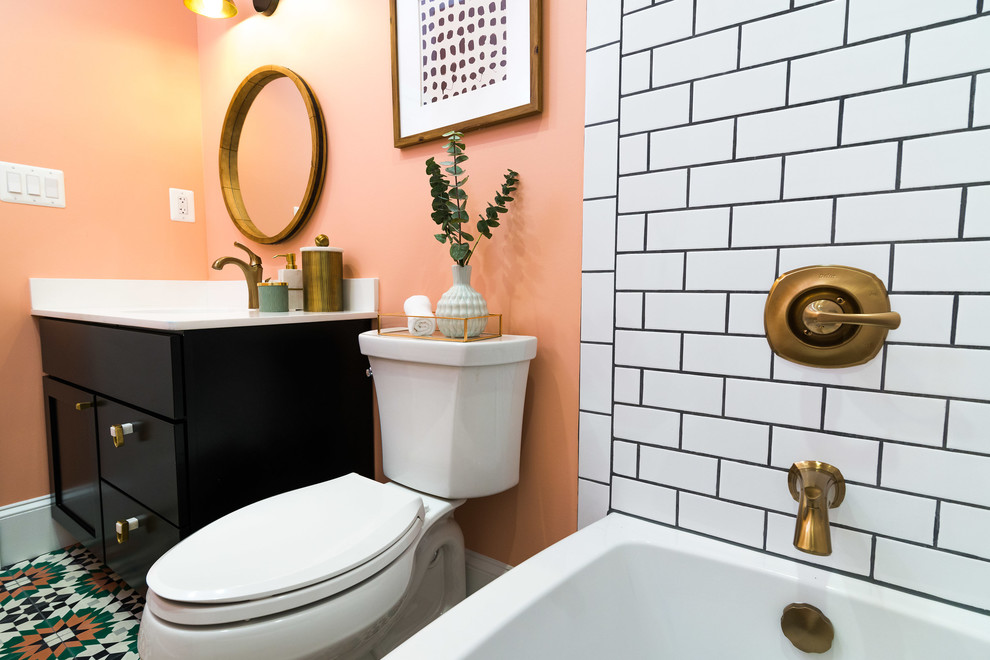 Inspiration for a mid-sized contemporary 3/4 white tile and subway tile multicolored floor and ceramic tile bathroom remodel in DC Metro with recessed-panel cabinets, black cabinets, a two-piece toilet, pink walls, an undermount sink, solid surface countertops and white countertops