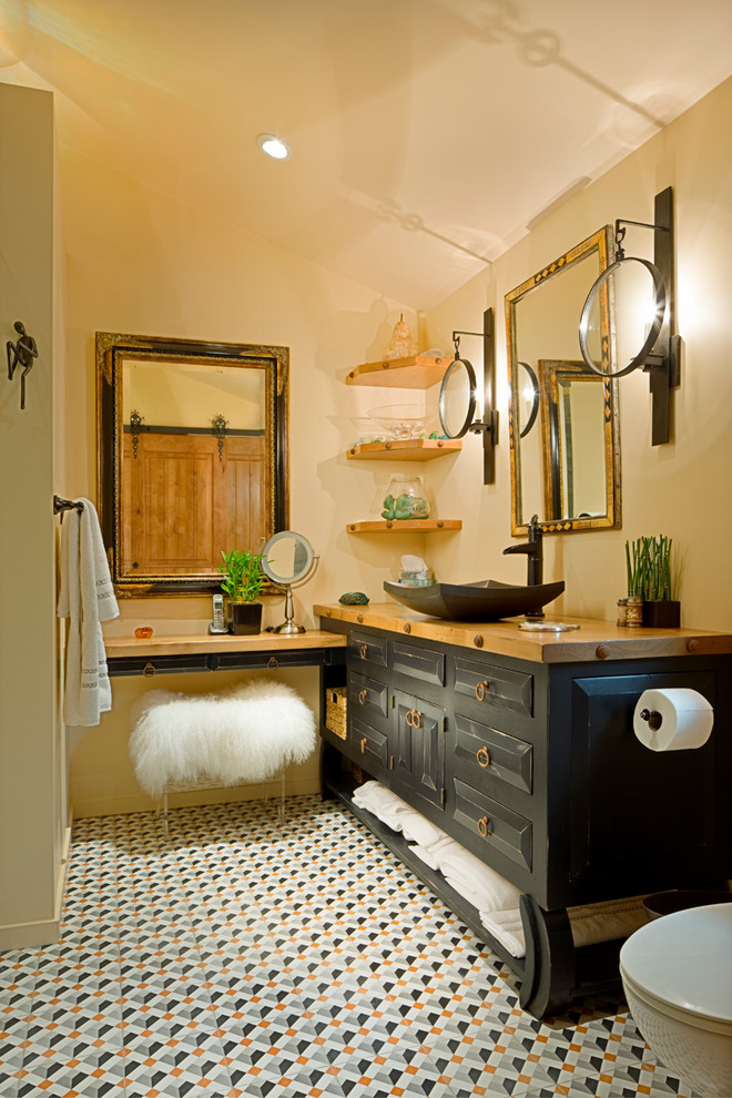 Example of a mid-sized transitional master porcelain tile and multicolored floor alcove shower design in Other with beige walls, raised-panel cabinets, black cabinets, a one-piece toilet, a vessel sink and wood countertops