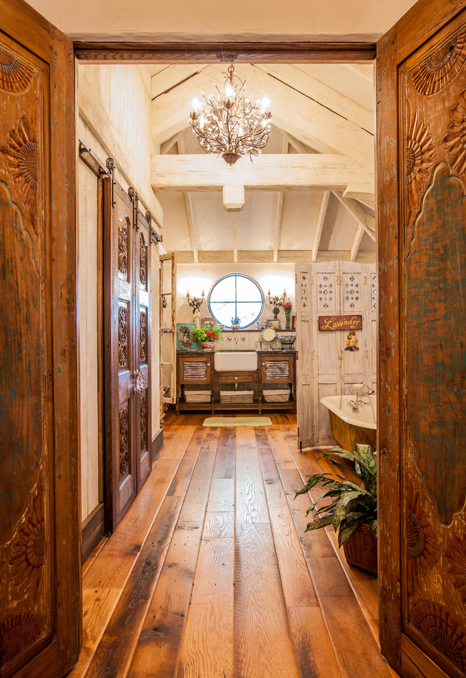 Bathroom - shabby-chic style medium tone wood floor bathroom idea in Dallas with an undermount sink, distressed cabinets, white walls and louvered cabinets