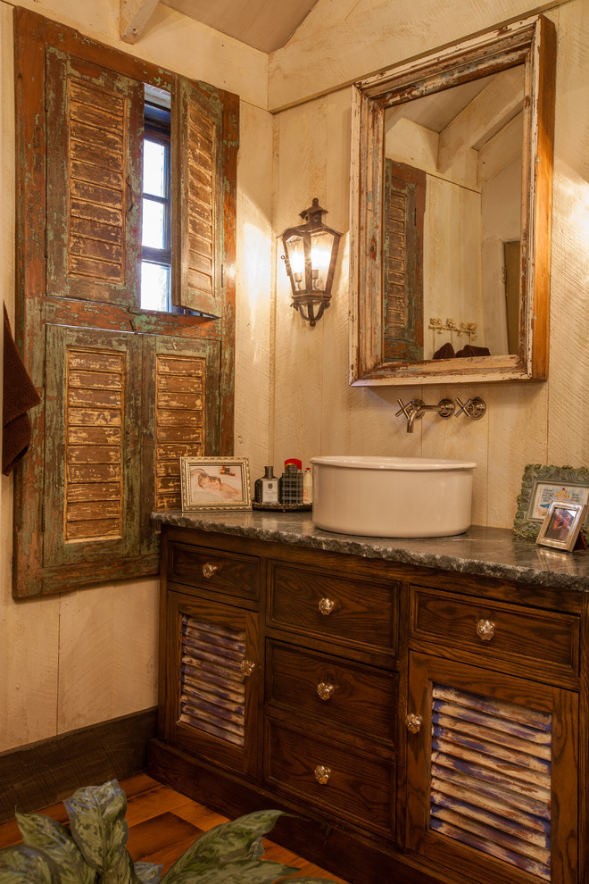 Inspiration for a rustic bathroom remodel in Dallas with a vessel sink, distressed cabinets and louvered cabinets
