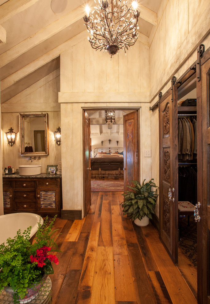 Inspiration for a rustic freestanding bathtub remodel in Dallas with a vessel sink, distressed cabinets and louvered cabinets
