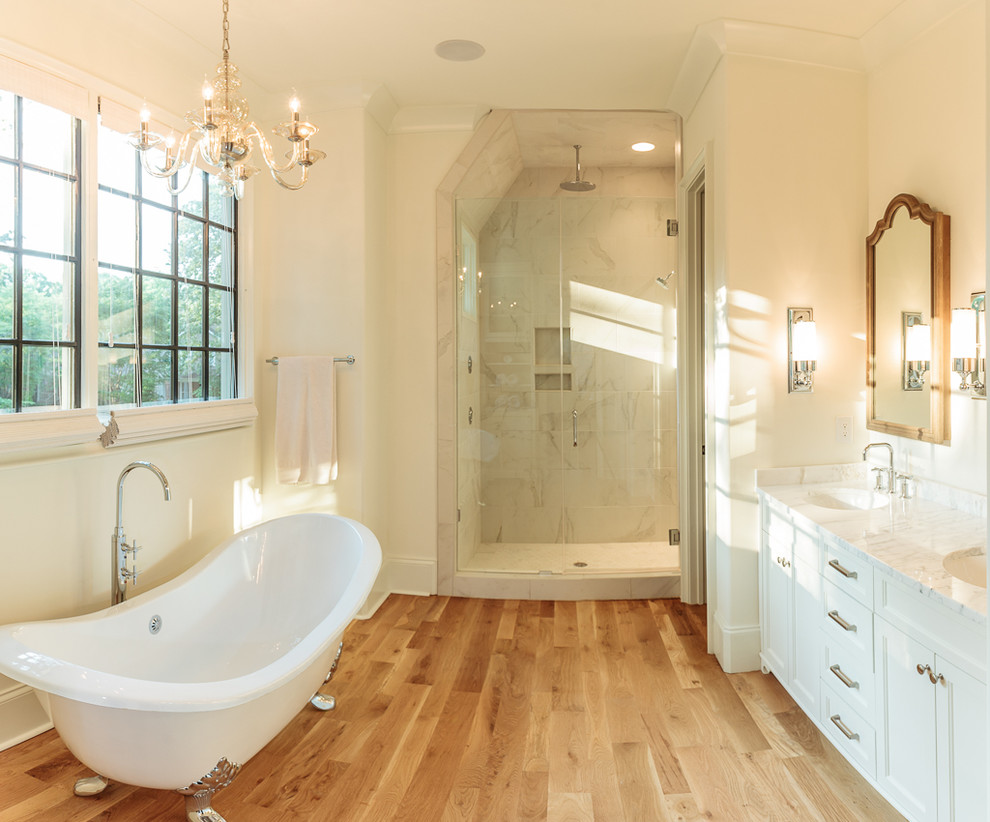 Example of a large transitional master claw-foot bathtub design in Charlotte with shaker cabinets, white cabinets, white walls and marble countertops