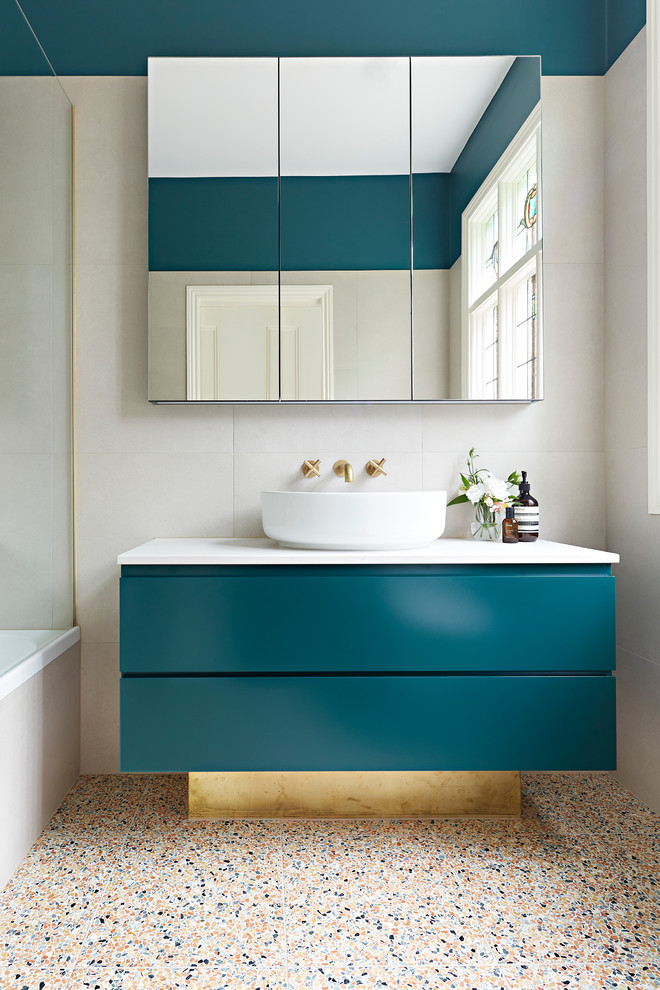 Example of a small trendy master beige tile and stone tile terrazzo floor and multicolored floor bathroom design in Melbourne with beige walls, a vessel sink, white countertops, green cabinets, a hinged shower door, furniture-like cabinets, a wall-mount toilet and quartz countertops