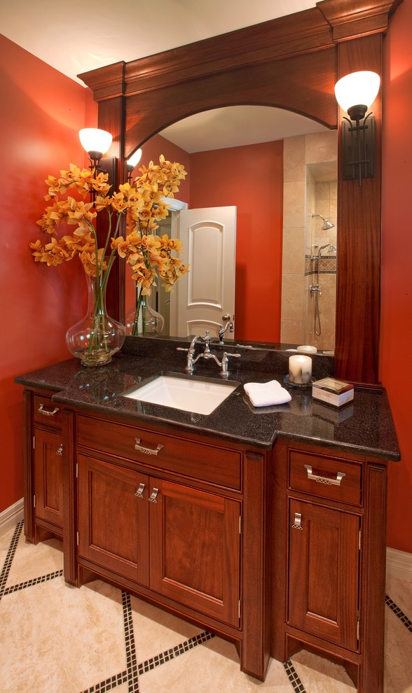 Example of a small classic beige tile and stone tile travertine floor bathroom design in Houston with an undermount sink, medium tone wood cabinets, granite countertops, a two-piece toilet, red walls and beaded inset cabinets