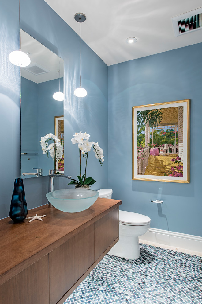 Beach style mosaic tile floor and blue floor bathroom photo in Kansas City with flat-panel cabinets, medium tone wood cabinets, a two-piece toilet, blue walls, a vessel sink, wood countertops and brown countertops