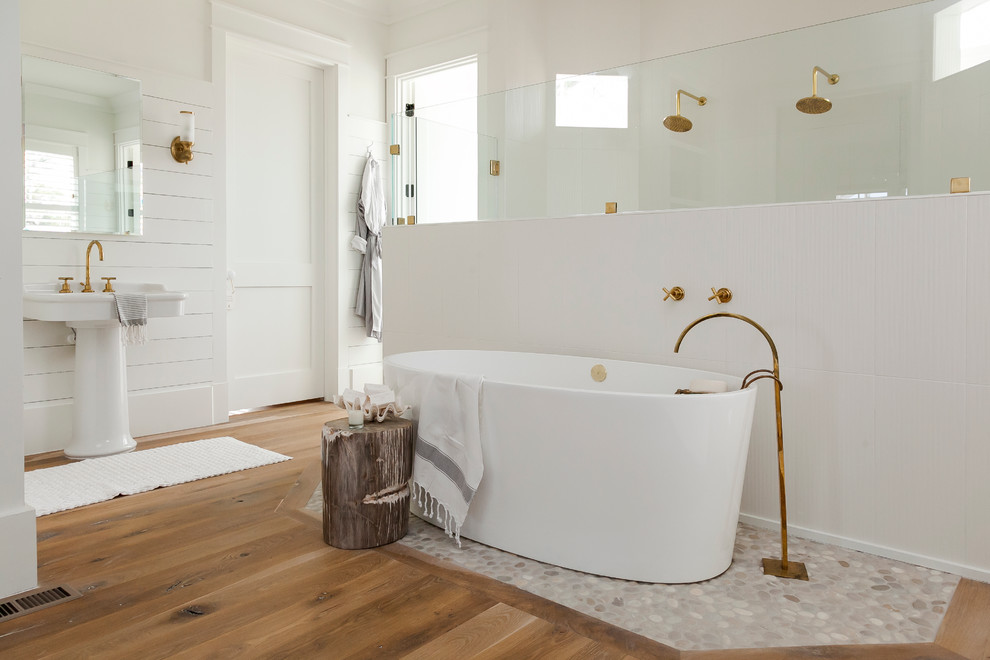 Beach style master medium tone wood floor bathroom photo in Charleston with a pedestal sink and white walls