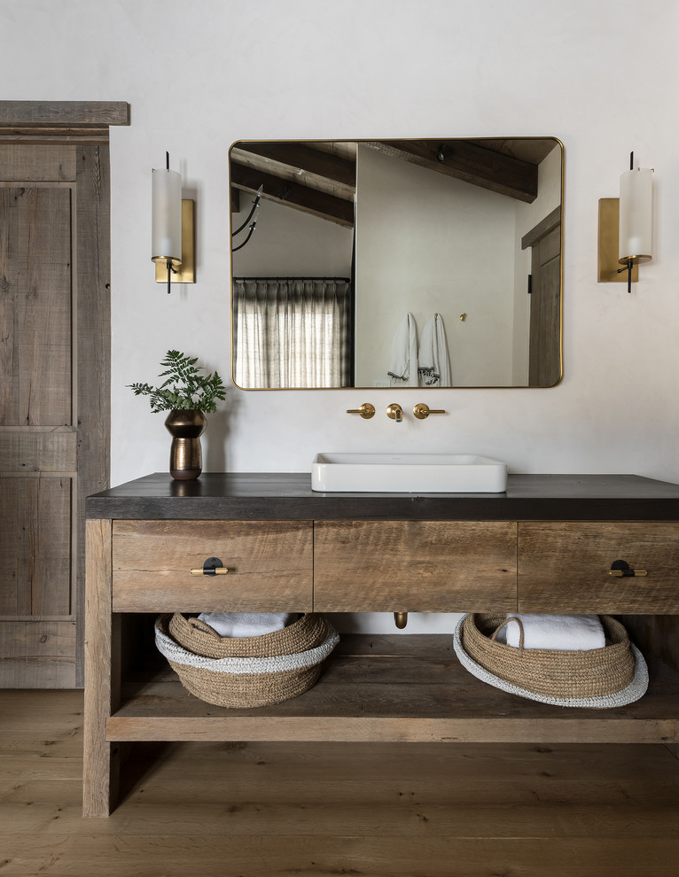 Mountain style medium tone wood floor and brown floor bathroom photo in Other with furniture-like cabinets, medium tone wood cabinets, white walls, a vessel sink and black countertops