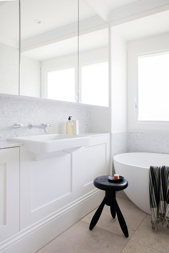 Inspiration for a contemporary bathroom in Sydney with shaker cabinets, white cabinets, a freestanding tub, gray tile, white tile, mosaic tile, white walls, a wall-mount sink and beige floor.