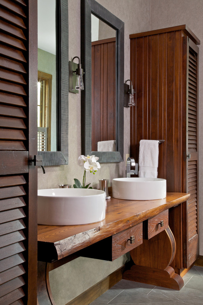 Example of a mountain style gray floor bathroom design in Other with furniture-like cabinets, medium tone wood cabinets, a vessel sink, wood countertops and brown countertops