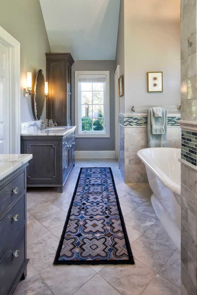 Inspiration for a timeless master gray tile and marble tile marble floor and gray floor bathroom remodel in New York with gray cabinets, beaded inset cabinets, a one-piece toilet, gray walls, an undermount sink, marble countertops, a hinged shower door and white countertops