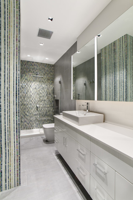 Mid-sized minimalist master multicolored tile and mosaic tile porcelain floor alcove shower photo in New York with flat-panel cabinets, white cabinets, a one-piece toilet, multicolored walls, a vessel sink and solid surface countertops