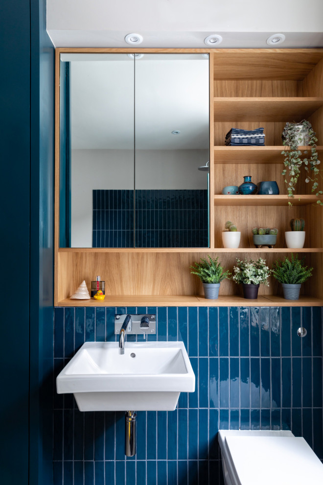 Inspiration for a mid-sized transitional kids' blue tile and ceramic tile porcelain tile, gray floor and single-sink bathroom remodel in London with flat-panel cabinets, blue cabinets, a wall-mount toilet, gray walls, a wall-mount sink, wood countertops, a hinged shower door, blue countertops and a built-in vanity