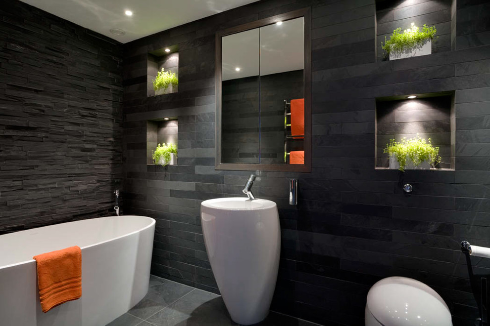 Bathroom - mid-sized contemporary kids' slate tile and gray tile slate floor and gray floor bathroom idea in London with a pedestal sink, recessed-panel cabinets, dark wood cabinets, a wall-mount toilet, gray walls and a niche