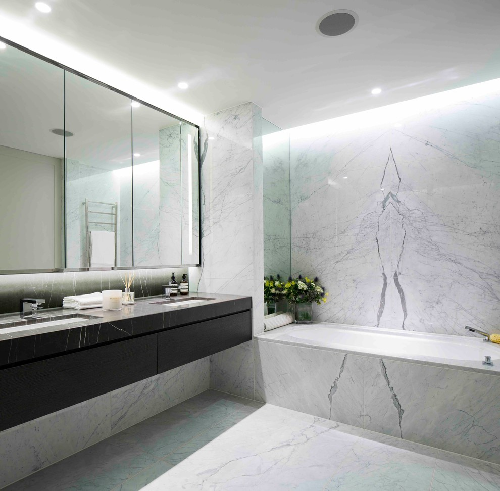 Bathroom - contemporary gray tile and marble tile marble floor bathroom idea in London with an undermount sink, an undermount tub and gray walls