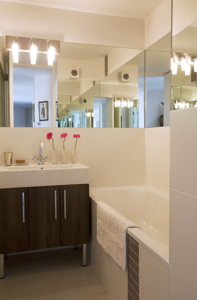 Inspiration for a contemporary white tile alcove bathtub remodel in London with a vessel sink, flat-panel cabinets and dark wood cabinets