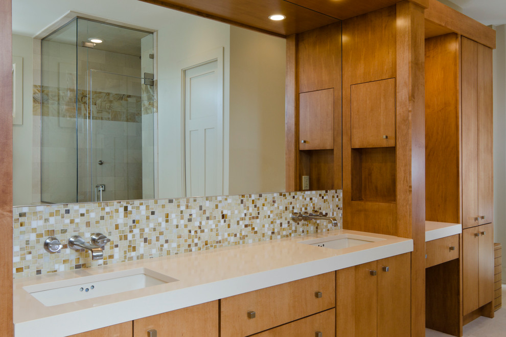 Large trendy master beige tile and stone tile alcove shower photo in Tampa with flat-panel cabinets, medium tone wood cabinets, an undermount tub, beige walls, an undermount sink, solid surface countertops and a hinged shower door