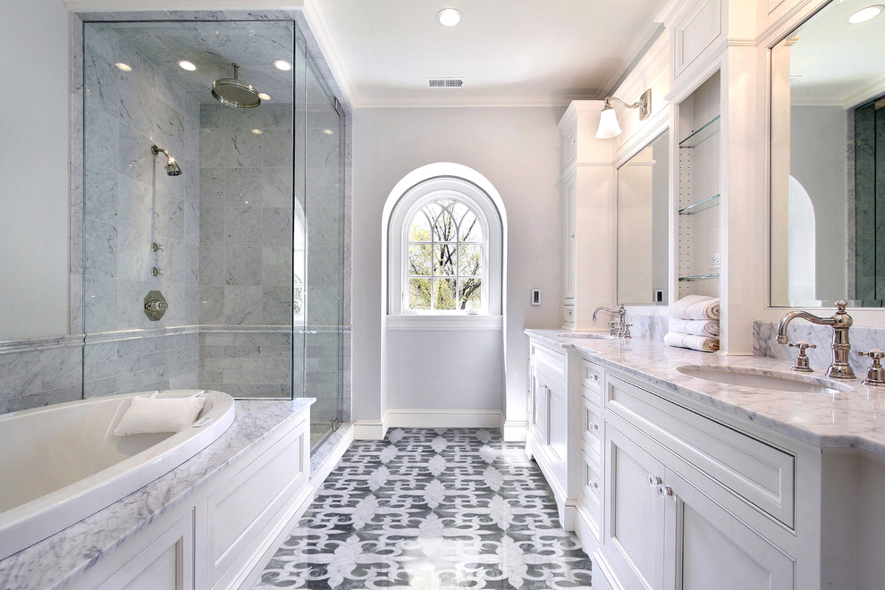 Inspiration for a large timeless master gray tile and marble tile marble floor and multicolored floor bathroom remodel in New York with recessed-panel cabinets, white cabinets, gray walls, an undermount sink, marble countertops and a hinged shower door