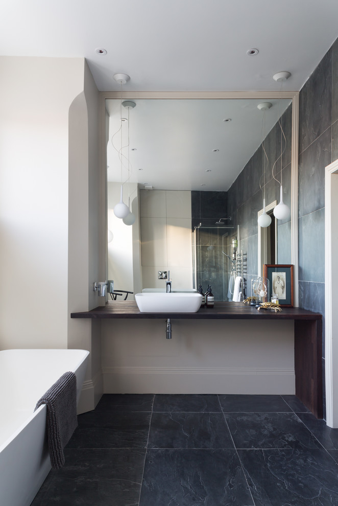 Inspiration for a scandinavian freestanding bathtub remodel in London with white walls, a vessel sink and wood countertops