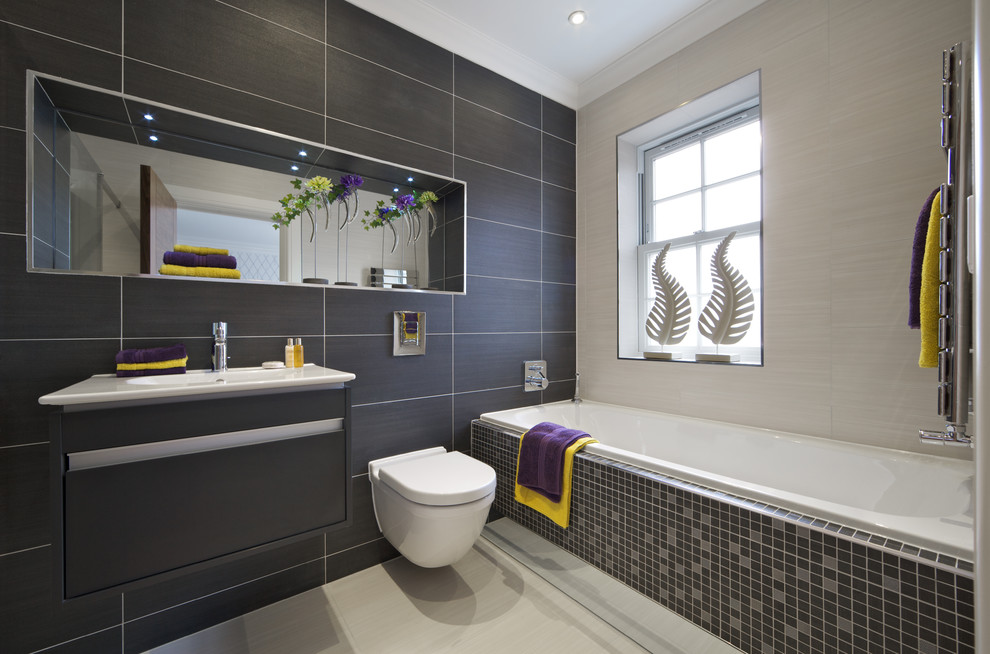 Example of a trendy gray tile and porcelain tile drop-in bathtub design in London with an integrated sink, flat-panel cabinets, gray cabinets and a wall-mount toilet
