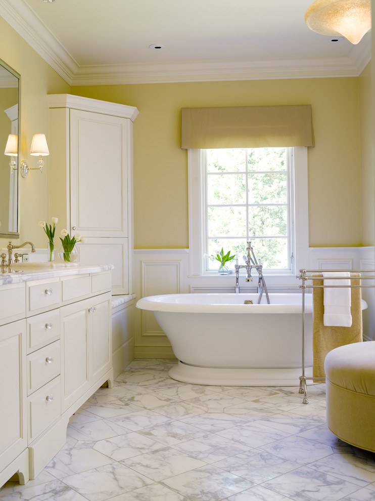 Example of a classic marble floor and white floor freestanding bathtub design in Seattle with yellow walls