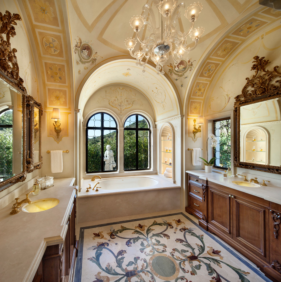Tuscan alcove bathtub photo in Santa Barbara with an undermount sink, dark wood cabinets and recessed-panel cabinets
