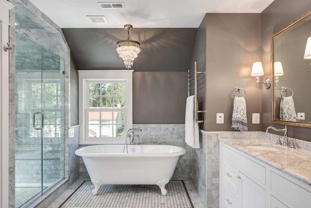 Example of a mid-sized classic master gray tile and marble tile marble floor and gray floor bathroom design in DC Metro with shaker cabinets, white cabinets, brown walls, an undermount sink, marble countertops, gray countertops and a hinged shower door