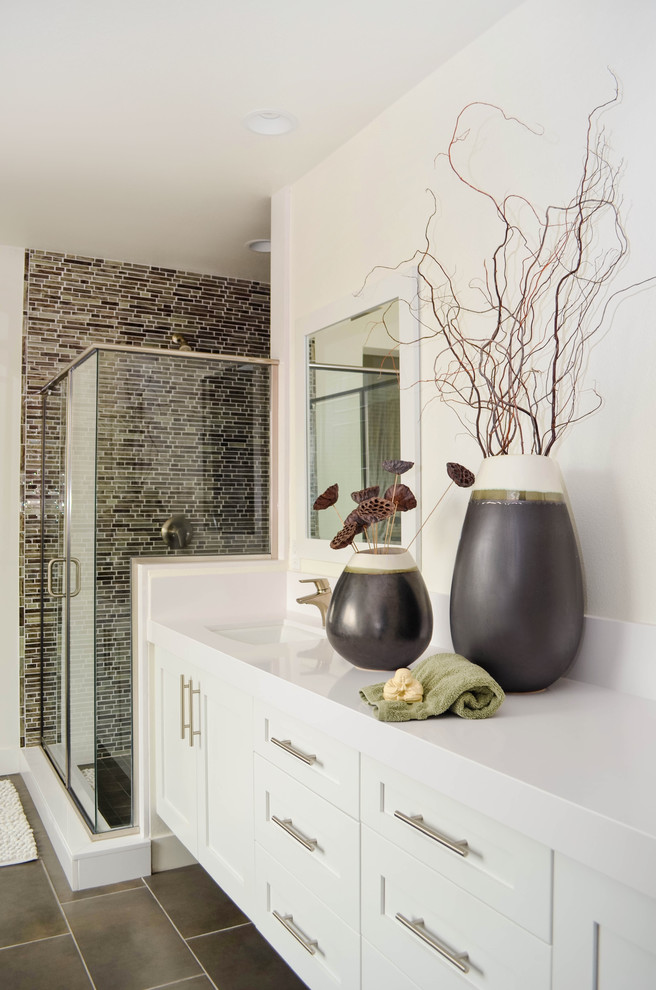 Bathroom - huge transitional master gray tile and glass sheet porcelain tile and gray floor bathroom idea in Los Angeles with shaker cabinets, white cabinets, a one-piece toilet, white walls, an undermount sink, solid surface countertops, a hinged shower door and white countertops