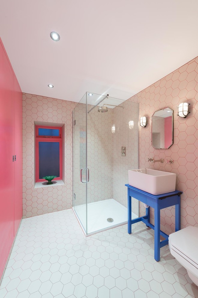 Example of a trendy 3/4 white tile corner shower design in London with a vessel sink, blue cabinets and pink walls