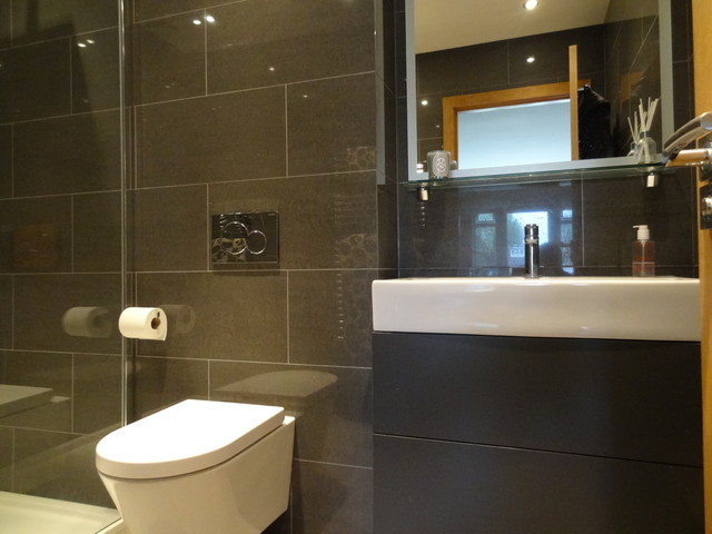 This is an example of a medium sized modern ensuite bathroom in London with a wall-mounted sink, glass-front cabinets, light wood cabinets, quartz worktops, a double shower, a one-piece toilet, brown tiles, ceramic tiles, grey walls and ceramic flooring.