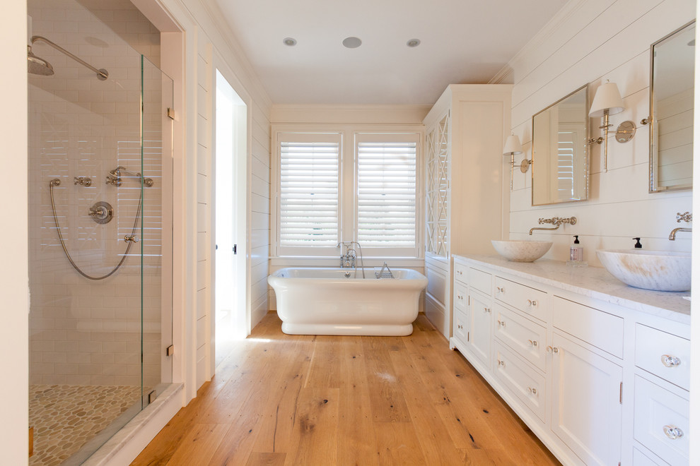 Inspiration for a large coastal master white tile and subway tile medium tone wood floor bathroom remodel in Boston with a vessel sink, recessed-panel cabinets, white cabinets, marble countertops and white walls