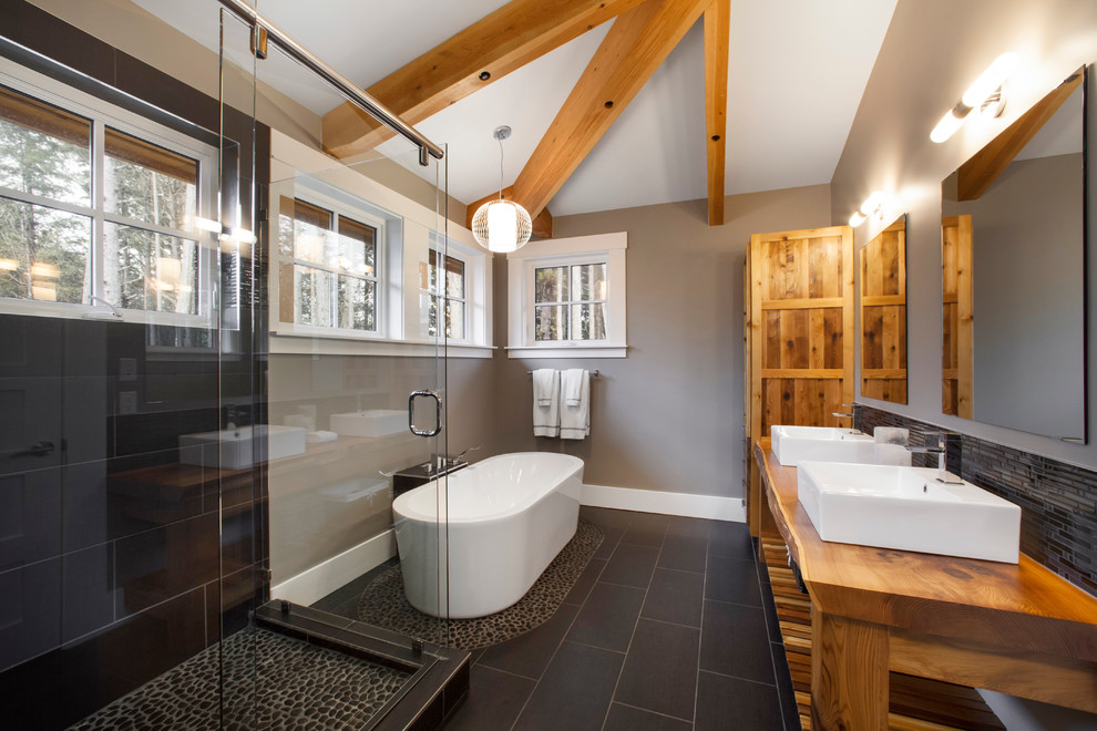 Freestanding bathtub - transitional pebble tile floor and black floor freestanding bathtub idea in Vancouver with a vessel sink, wood countertops and brown countertops