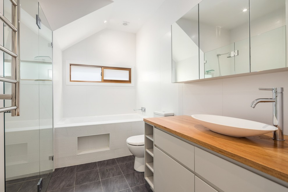 Photo of a mid-sized contemporary master bathroom in Sydney with furniture-like cabinets, white cabinets, an alcove tub, an alcove shower, a two-piece toilet, white tile, cement tile, white walls, ceramic floors, a vessel sink and wood benchtops.