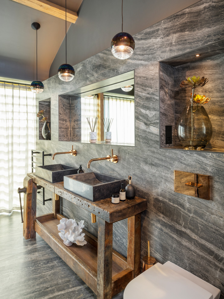 Trendy gray tile gray floor, double-sink, exposed beam and vaulted ceiling bathroom photo in Cornwall with open cabinets, dark wood cabinets, gray walls, a vessel sink, wood countertops, brown countertops and a freestanding vanity