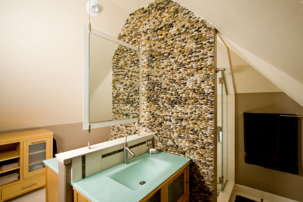 Example of a trendy pebble tile bathroom design in Denver with an integrated sink