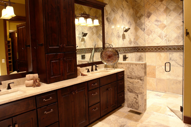 Mid-sized mountain style master beige tile and stone tile travertine floor and beige floor walk-in shower photo in Denver with an undermount sink, raised-panel cabinets, dark wood cabinets, beige walls, granite countertops and a hinged shower door