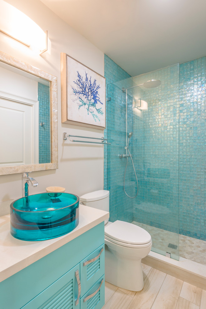 Example of a mid-sized beach style master blue tile and glass tile light wood floor and beige floor alcove shower design in Miami with louvered cabinets, blue cabinets, a two-piece toilet, beige walls, a vessel sink, quartz countertops, a hinged shower door and beige countertops