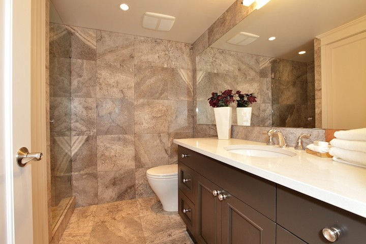 Example of a small trendy 3/4 beige tile and stone tile porcelain tile alcove shower design in Vancouver with shaker cabinets, black cabinets, an undermount sink, solid surface countertops, a two-piece toilet and beige walls