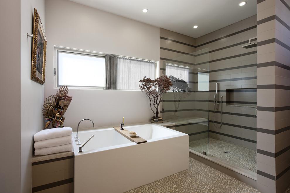 Trendy pebble tile floor freestanding bathtub photo in Los Angeles