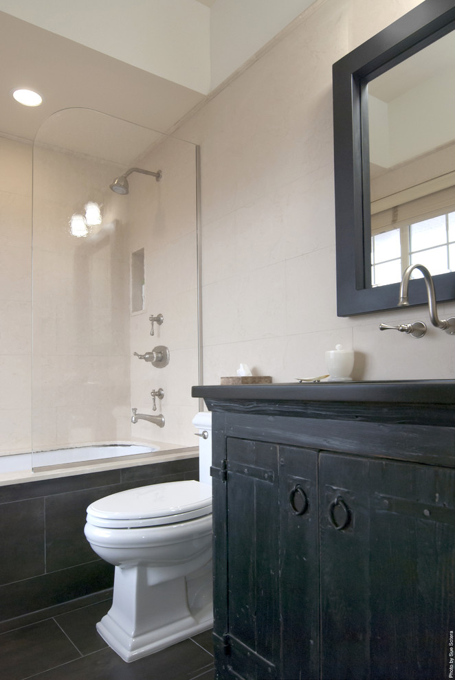 Mountain style beige tile bathroom photo in New York with an undermount sink and black cabinets