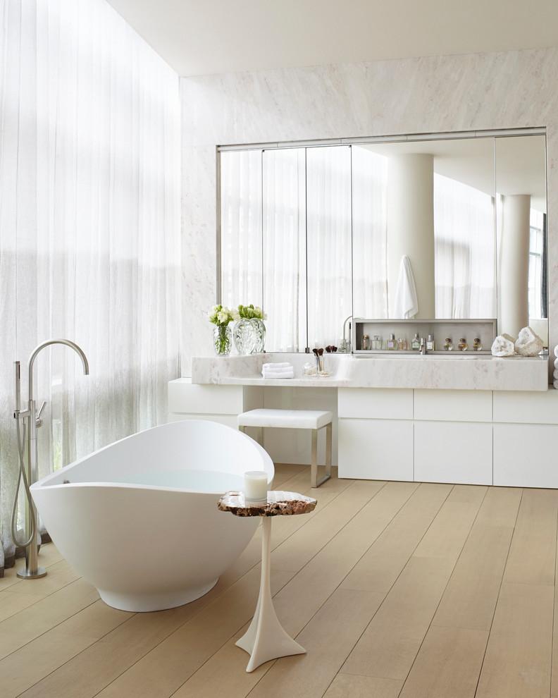 Diseño de cuarto de baño actual con armarios con paneles lisos, puertas de armario blancas, bañera exenta y suelo de madera en tonos medios