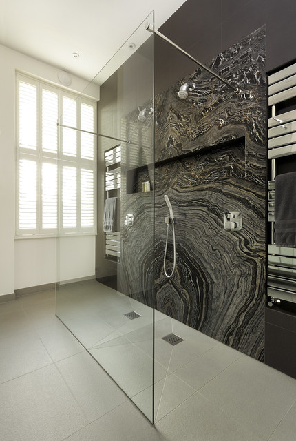 Example of a trendy master marble tile doorless shower design in London with black walls