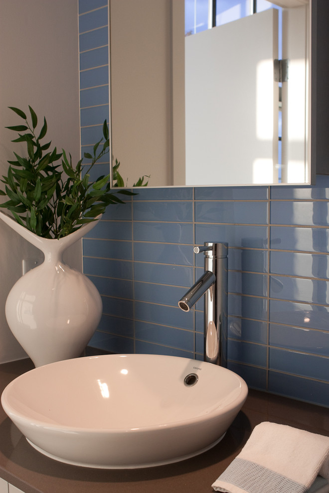 Inspiration for a contemporary bathroom remodel in Vancouver with solid surface countertops and a drop-in sink