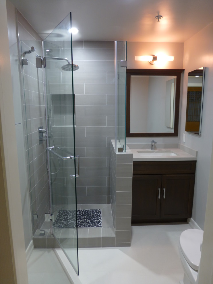 Inspiration for a small contemporary 3/4 gray tile and porcelain tile porcelain tile corner shower remodel in Los Angeles with an undermount sink, recessed-panel cabinets, dark wood cabinets, quartz countertops, gray walls and a one-piece toilet