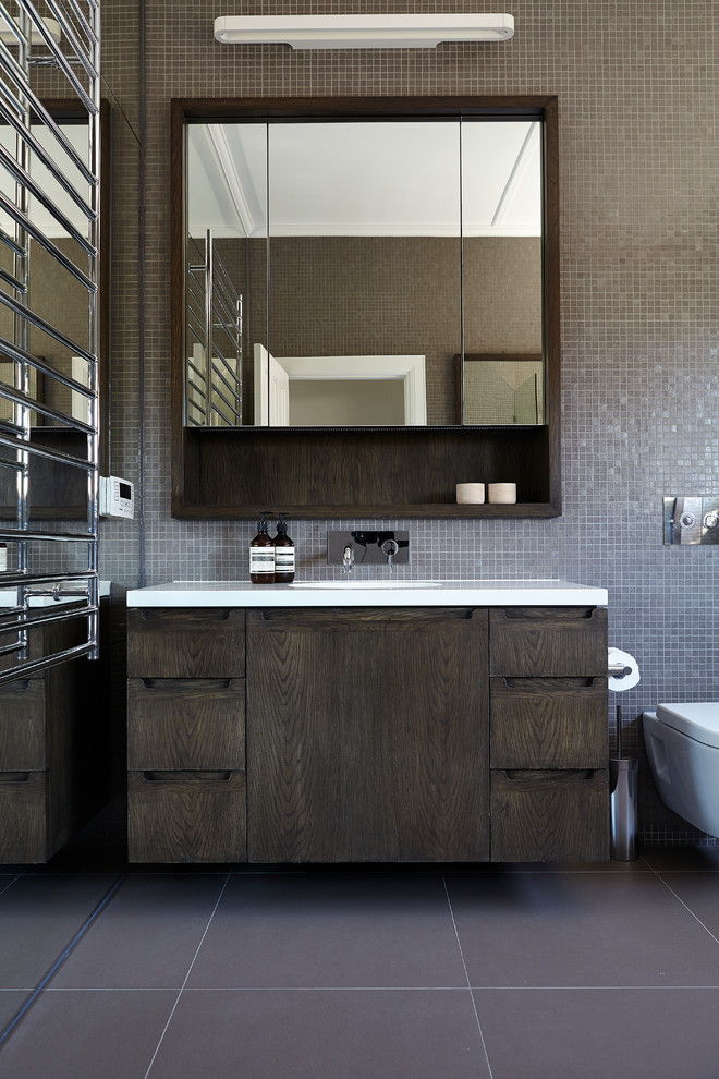 Inspiration for a mid-sized contemporary brown tile and mosaic tile bathroom remodel in Melbourne with flat-panel cabinets, dark wood cabinets, a wall-mount toilet, brown walls and white countertops