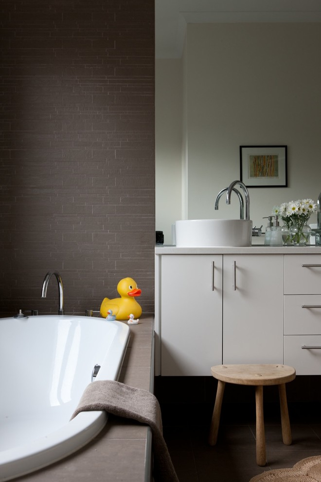 Example of a trendy gray tile drop-in bathtub design in Adelaide with a vessel sink, flat-panel cabinets and gray cabinets