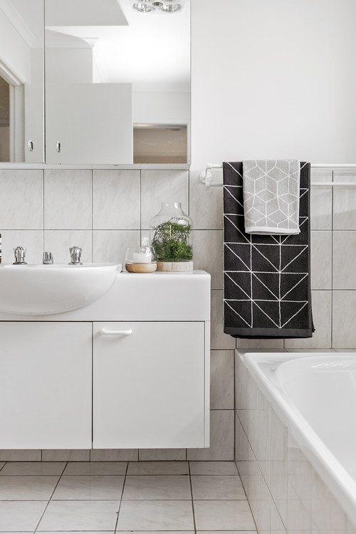 plain white bathroom with patterned towels